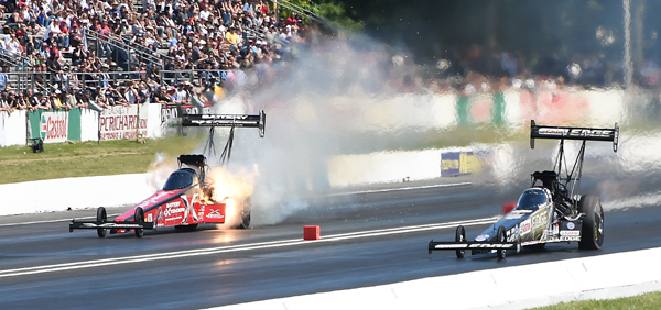 First round action featured Brittany Force (near lane) defeating Spencer Massey as Massey loses an engine